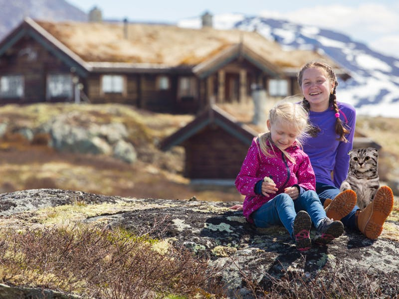 Barn sittende foran hytta