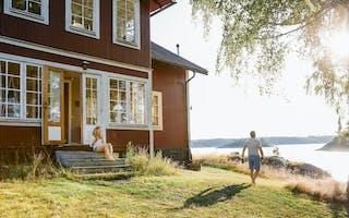 Dame og mann ved rødt hus ved sjøen