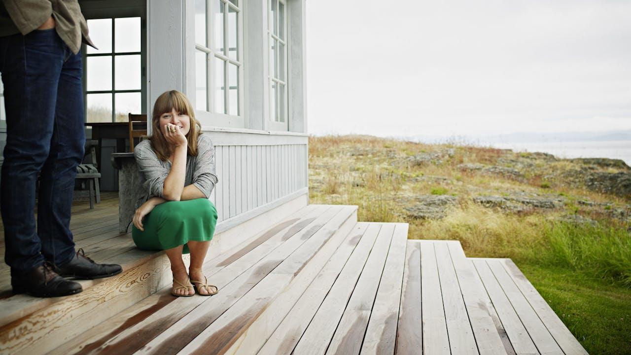 Dame sitter i trapp på hus ved sjøen