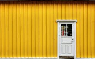 Gul husvegg med hvit dør