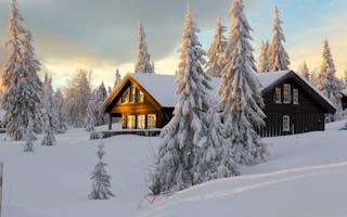 Hytte i snøkledd landskap med solnedgang
