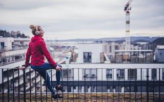 Kvinne sitter på taket av et nybygg