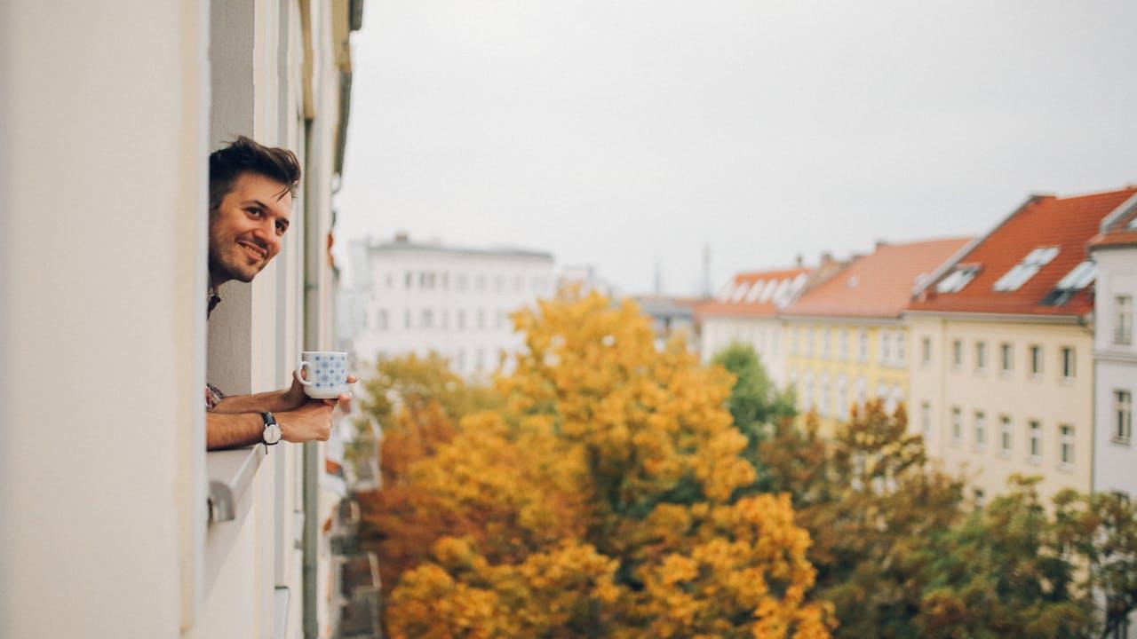 Mann lener seg ut av vindu på leilighet med trær utenfor