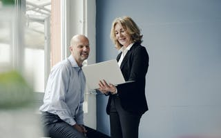 Mann og kvinne ser på laptop
