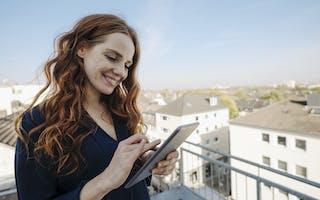 Rødhåret kvinne bruker nettbrett på takterrasse