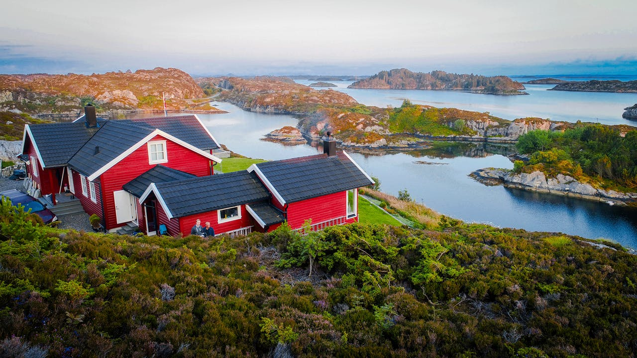 Rødt hus på svaberg ved sjøen