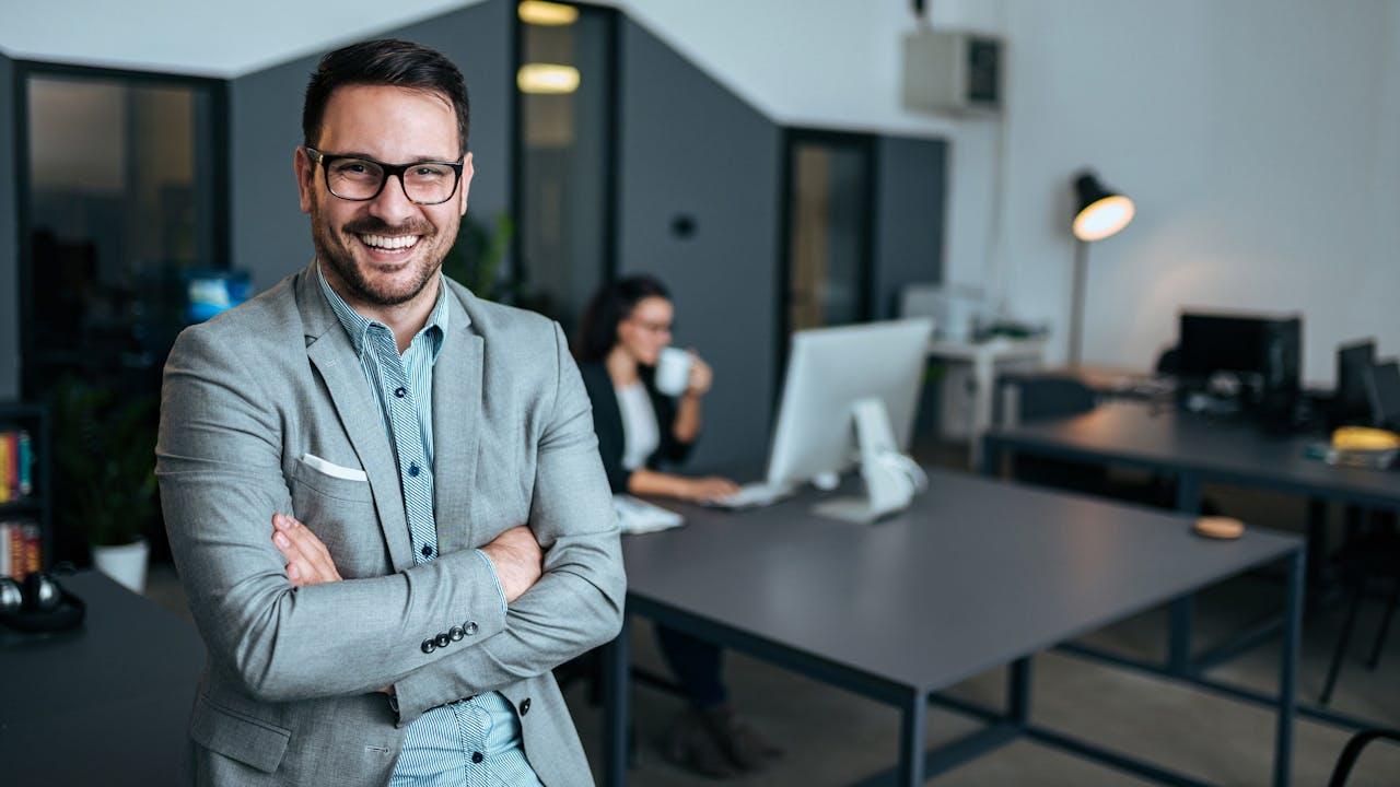 Smilende mann i kontorlandskap