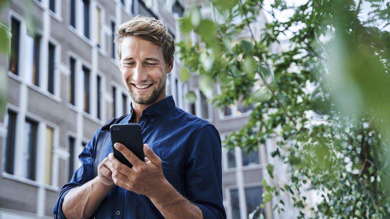 Smilende ung mann ser på mobil