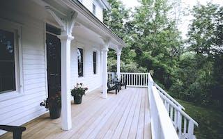 Terrasse foran hvitt hus med hage
