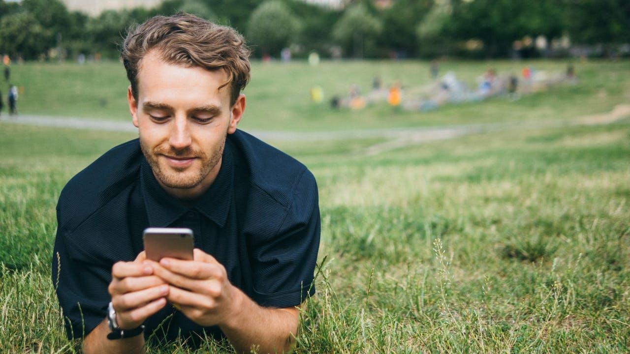 Ung mann leser på mobilen i park