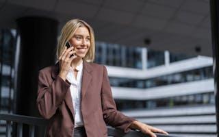 Kvinne i brun dress smiler og snakker i telefonen