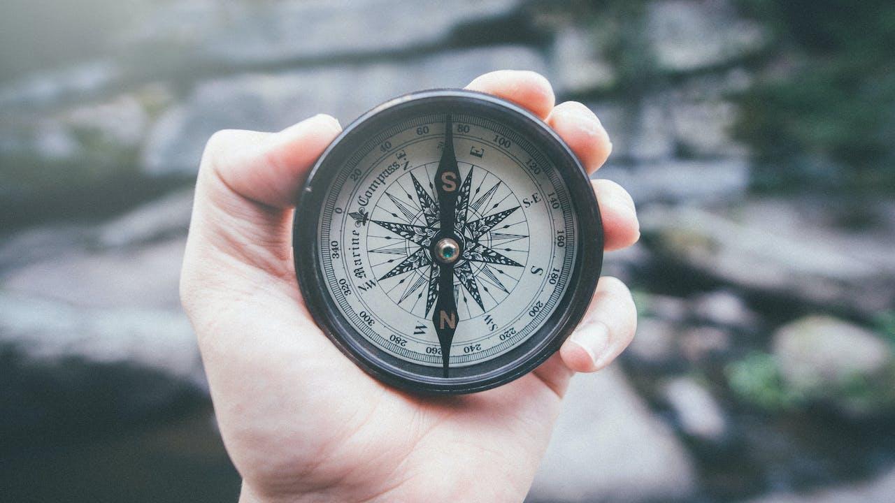 Hånd med kompass foran fjell