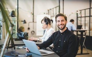 Smilende mann med kollega i kontorlandskap