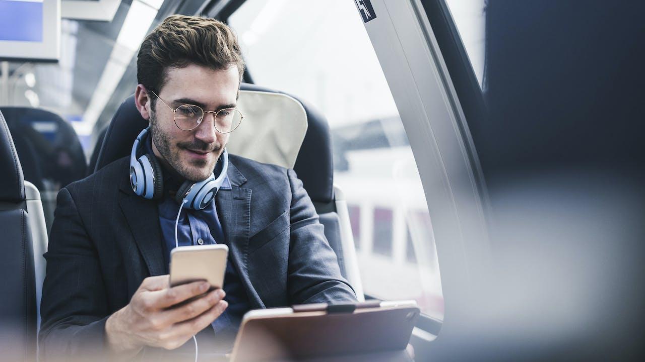 Ung mann med briller leser nettbrett på tog