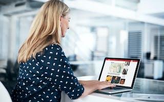 Kvinne jobber på laptop i kontorlandskap
