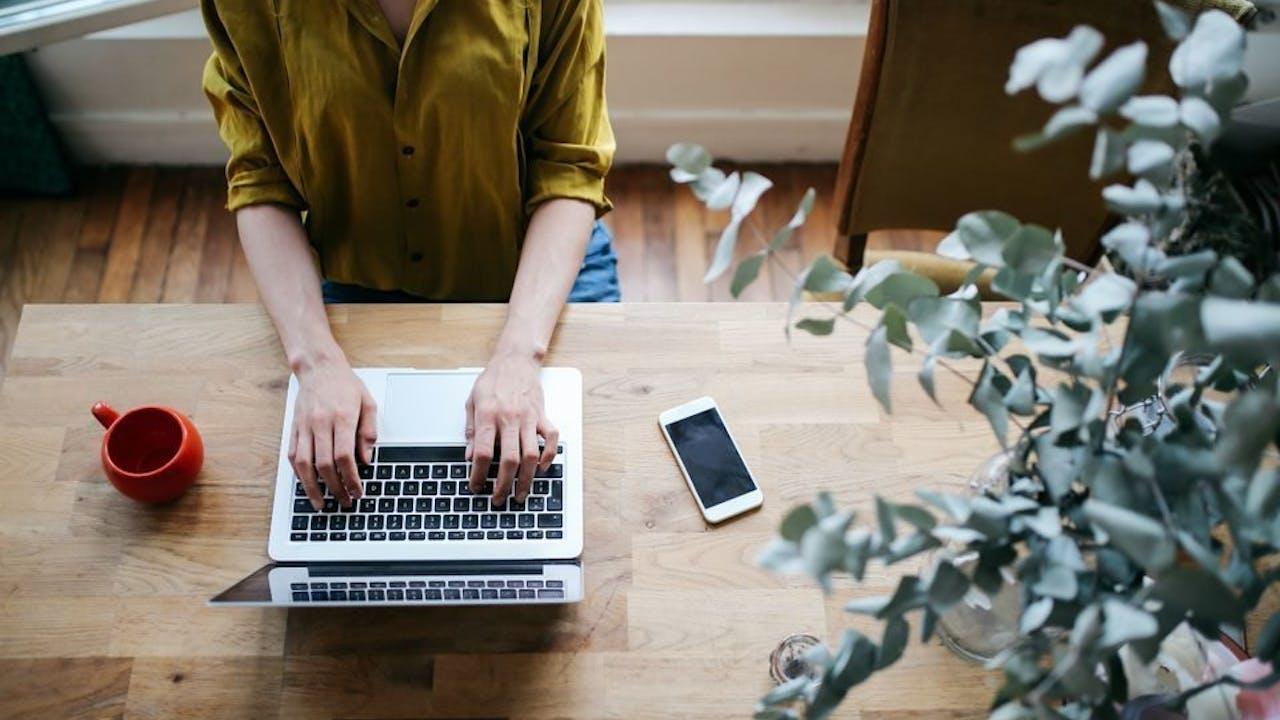 Kvinne skriver på laptop sett ovenfra