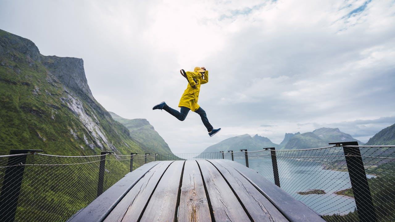 Person med gul jakke hopper ved utsiktspunkt