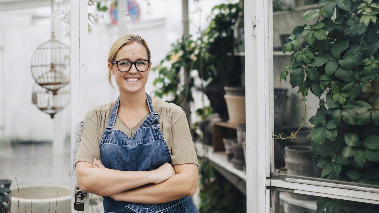 Smilende kvinne med forkle står i døråpning