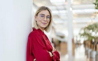 Smilende ung kvinne med rød bluse og briller