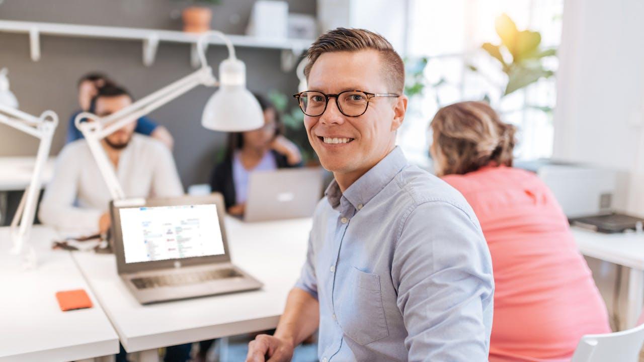 Ung mann med briller på kontor med kollegaer