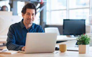 Mann jobber på laptop