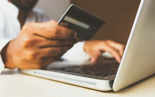 En hånd holder kredittkort og laptop