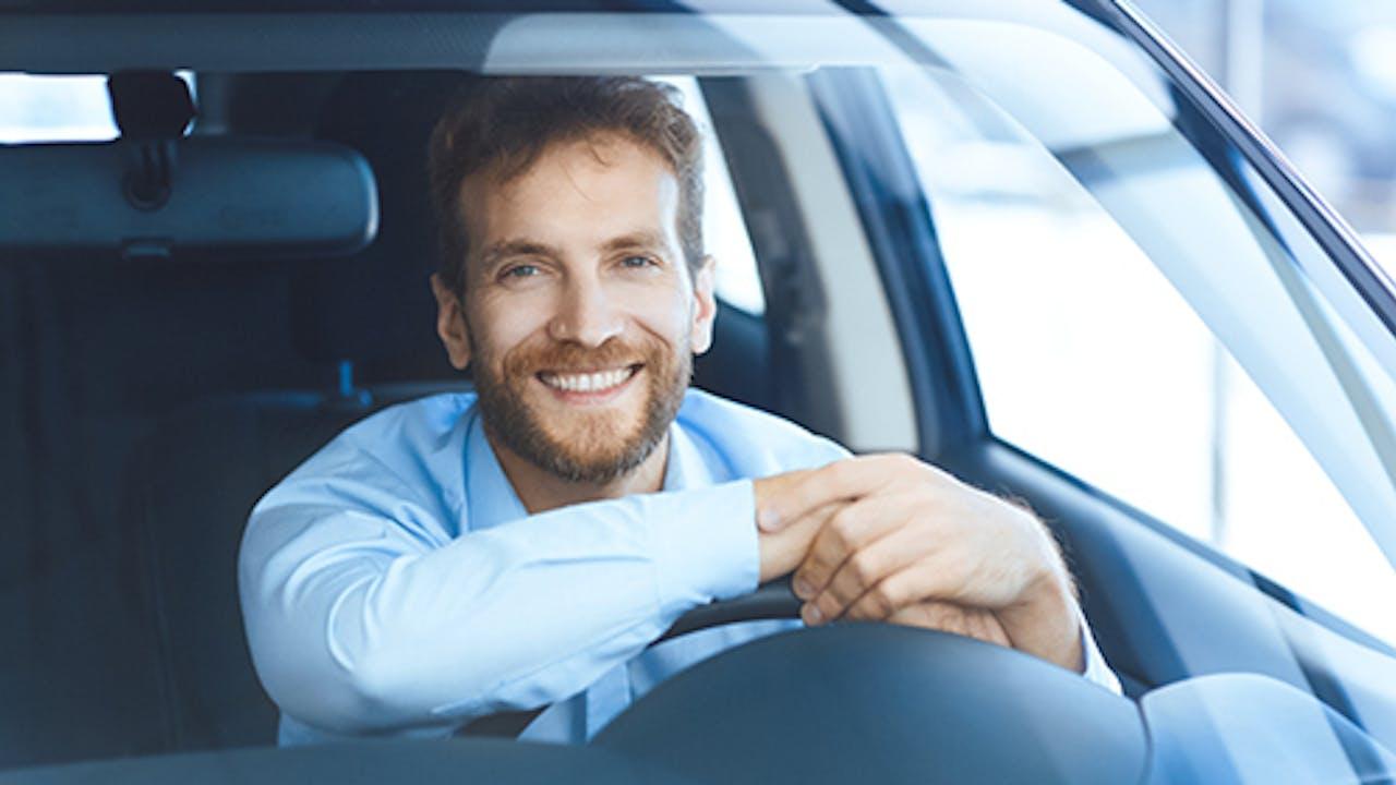Smilende mann i bil