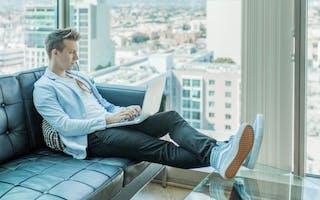 Mann i sofa med laptop og utsikt