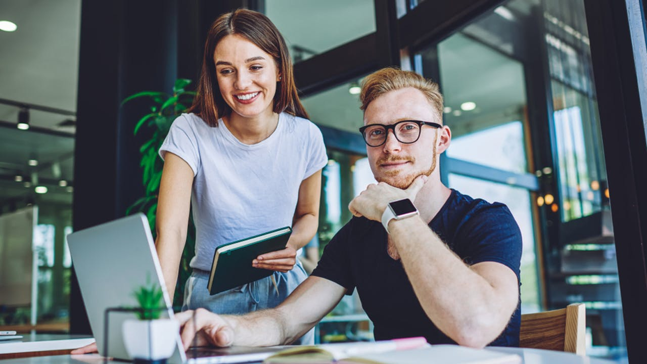 Mann og dame foran laptop