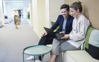 Mann og dame sitter i korridor med laptop