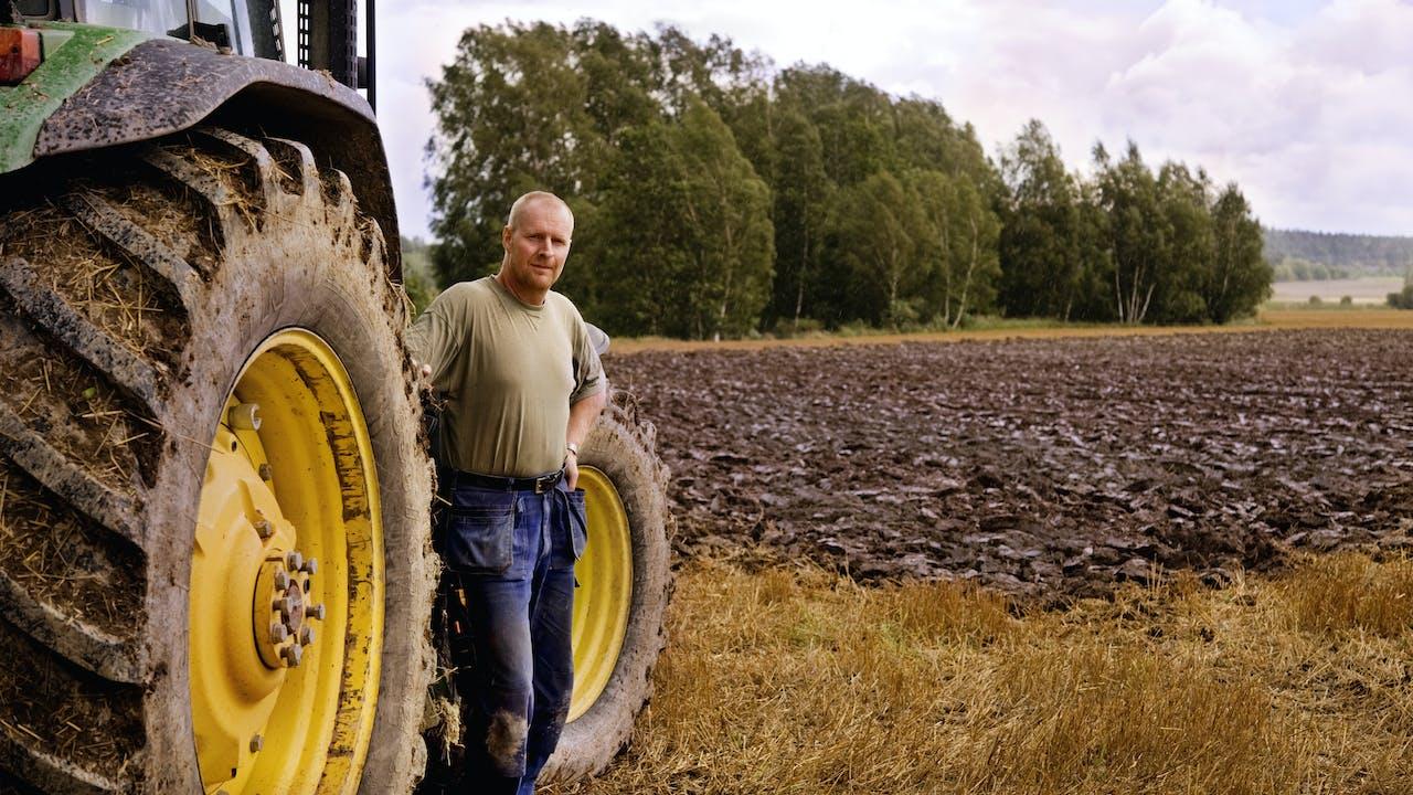 Bonde med traktor på åker