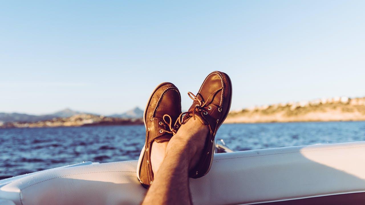Føtter med seilersko på båt