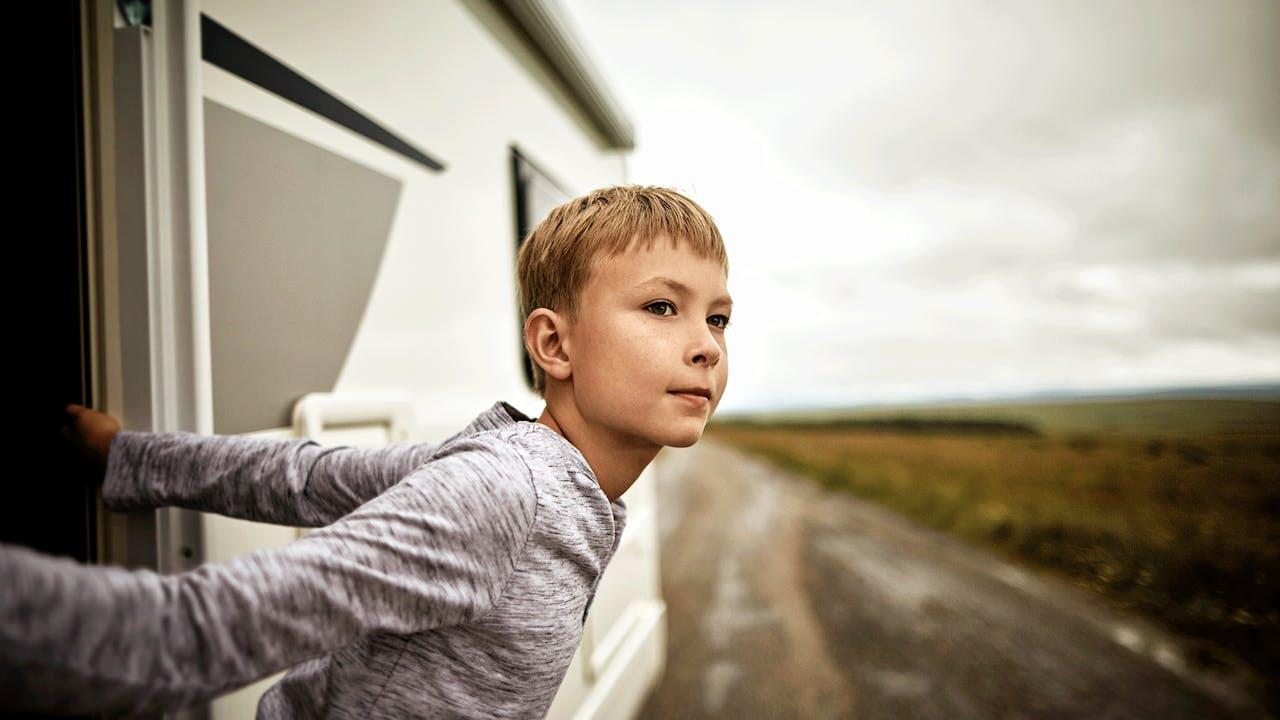Gutt lener seg ut av bobil
