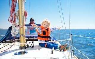 Liten gutt med redningsvest på dekk av seilbåt