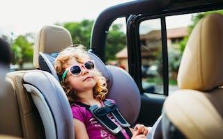Liten jente med solbriller i cabriolet