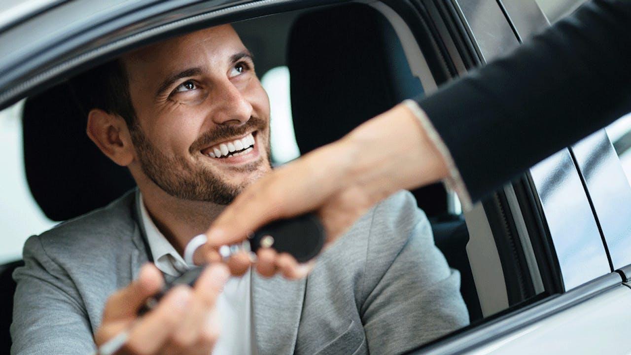Mann i bil får nøkler av bilselger
