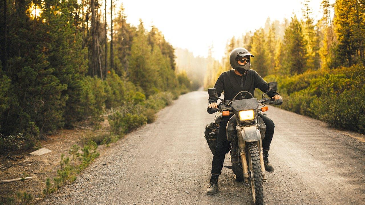 Mann på motorsykkel i skogen