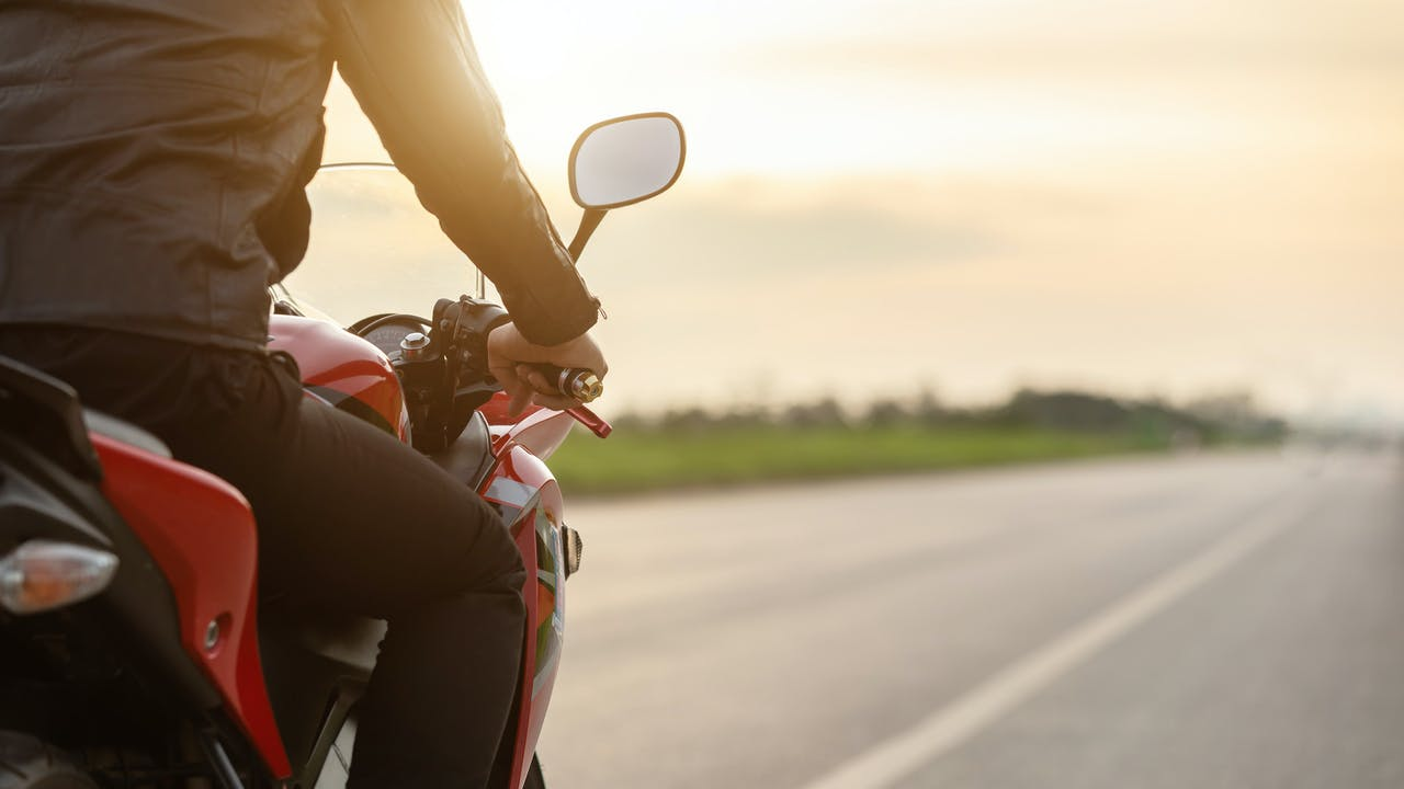 Mann på motorsykkel i solnedgang