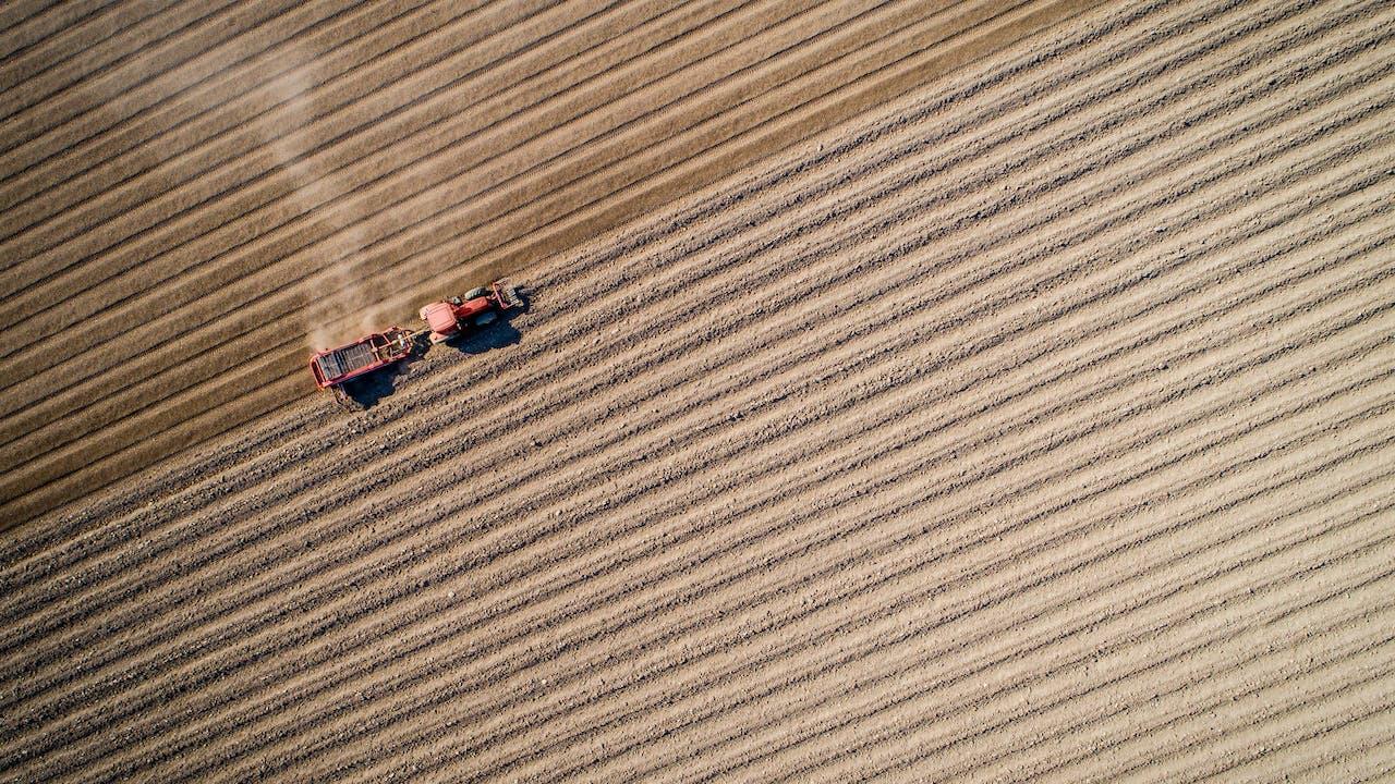 Bildet viser en traktor på et jorde i Ringsaker, tatt ovenfra