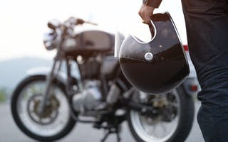 Motorsykkel med hånd som holder hjelm