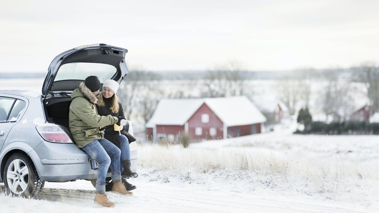 Par sitter i enden av en bil i vinterlandskap