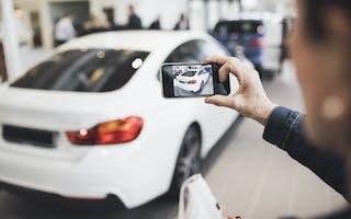 Person filmer bil med mobiltelefon