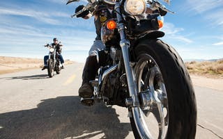 Bilde av to motorsykler på en hovedvei med blå himmel og lett skydekke i bakgrunnen