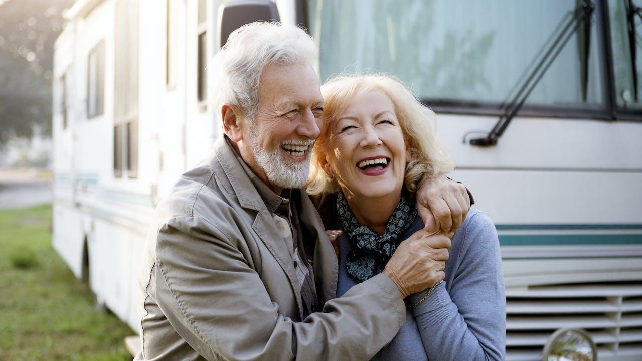 Smilende eldre par utenfor bobil