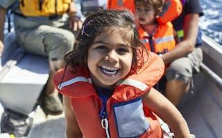 Smilende jente med redningsvest på båt