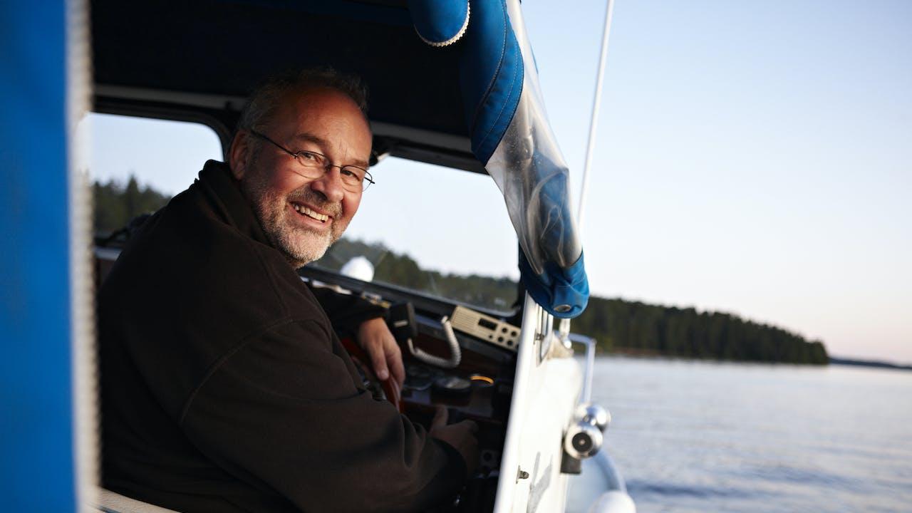 Smilende mann i båt på sjøen