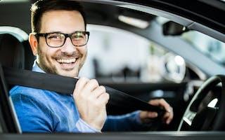 Smilende mann tar på seg bilbelte