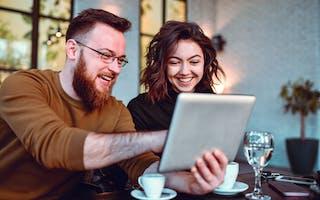 Smilende par ser på nettbrett