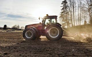Traktor på jorde i sollys