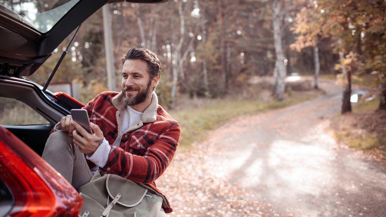 Ung mann med mobil i bagasjerommet av bil
